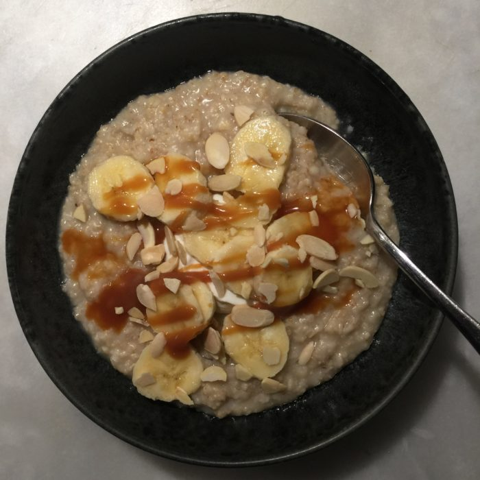 porridge or oatmeal with bananas, creme fraiche, caramel and slivered almonds